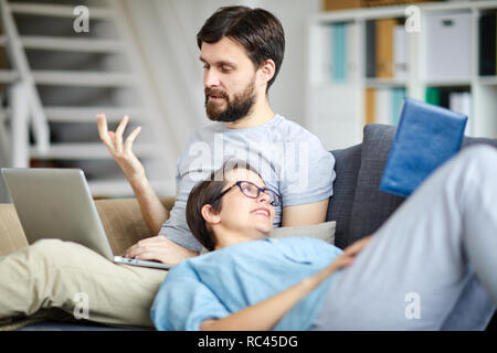 Young relaxed couple discussing possible plans for the following weekend while lying on sofa - Stock Image