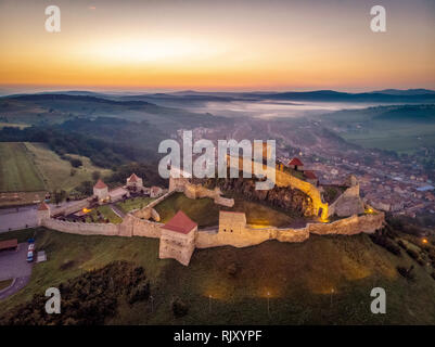 Transylvania from above at sunrise. The Rupea Fortress and Rupea Village - Stock Image