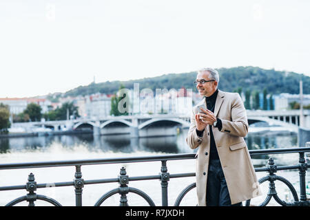 Mature handsome businessman with smartphone standing by river Vltava in Prague city at sunset, texting. Copy space. - Stock Image