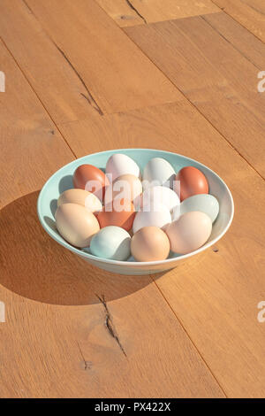 a bowl of various coloured eggs on a wooden surface - Stock Image
