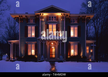 Stately Victorian Inn with winter snowfall in Cooperstown is welcoming at night, New York, USA - Stock Image