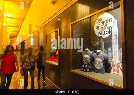 Manhattan, New York, U.S. - May 21, 2014 - At 30 Rockefeller Center, visitors walk by NBC studios display case with souvenir T-shirts and mugs for The Tonight Show starring Jimmy Fallon, during a pleasant Spring day in Rockefeller Plaza, midtown Manhattan. - Stock Image
