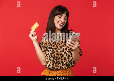 Image of a beautiful happy young woman dressed in animal printed shirt posing isolated over red background holding credit card using mobile phone. - Stock Image