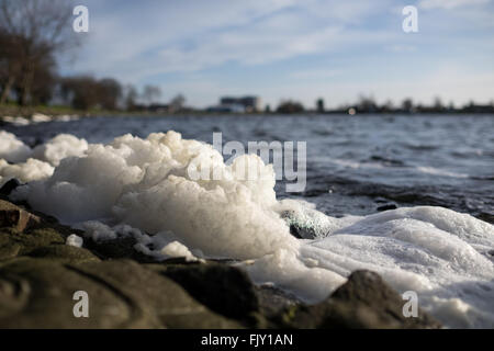 Close-Up Of Surf At Beach On Sunny Day - Stock Image