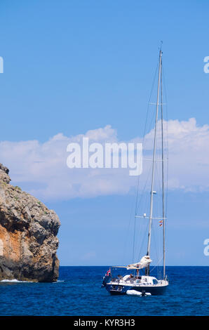 View of a yacht with rocky coast at Cala Deia Beach in Mallorca, Spain. - Stock Image
