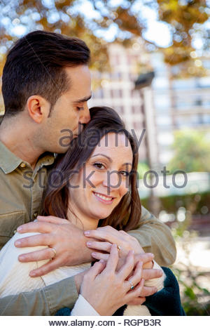 A man hugs and kisses his young wife from behind in a public park - Stock Image