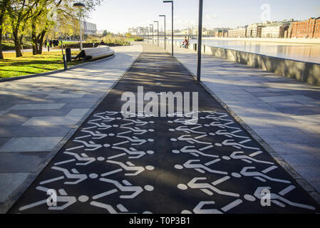 Pedestrian crossing sign on asphalt in city public park. The walking man. Permission to walk pedestrians. - Stock Image
