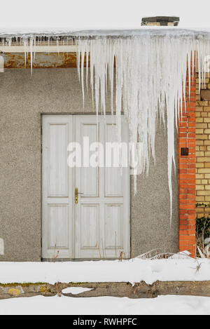 Huge icicles hang from the roof of an abandoned house with wooden door. - Stock Image