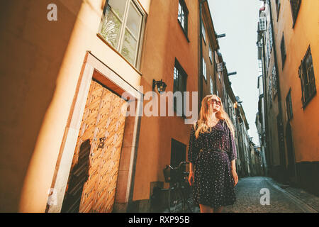 Young woman walking in Stockholm city excursion traveling in Sweden lifestyle summer Europe vacations - Stock Image