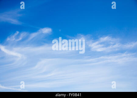 White cirrus cloud on in blue sky in UK springtime. - Stock Image