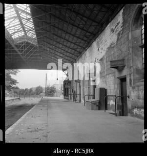 Tadcaster Station, Station Road, Tadcaster, North Yorkshire, 1966-1970. A view looking north along the platform of the abandoned Tadcaster railway station with the Tower Brewery visible in the background. The tracks have been lifted after the closure of the line. - Stock Image