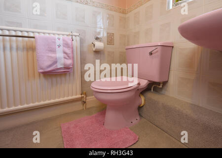 An old fashioned pale pink coloured bathroom toilet - Stock Image