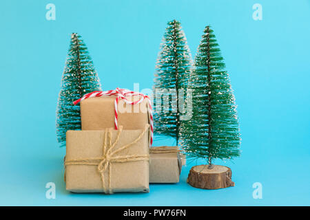 Pile of gift boxes wrapped in craft paper tied with twine red white ribbon Christmas trees on mint blue background. New Year corporate presents shoppi - Stock Image
