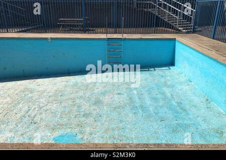 Swimming pool without water, on a beautiful sunny day with shadow cast on pool wall. - Stock Image