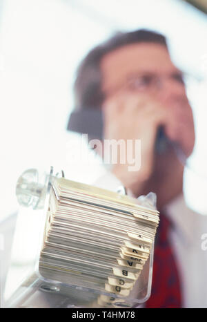 Businessman at desk working with his rolodex card index, NYC, USA - Stock Image