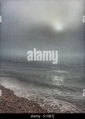 Eerie scene at the beach revealing navigation marker post in water through the mist. - Stock Image