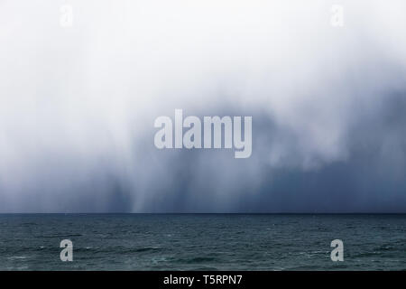stormy clouds and heavy rain on the sea - Stock Image