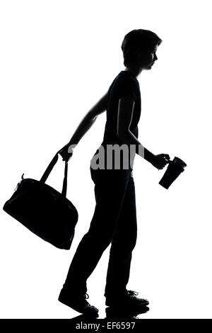 one caucasian young teenager silhouette school boy or girl walking full length in studio cut out isolated on white - Stock Image