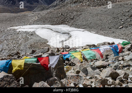 Group of pilgrims crossing the glacier in valley en route Mount Kailash Kora, a view from Dolma La pass. - Stock Image