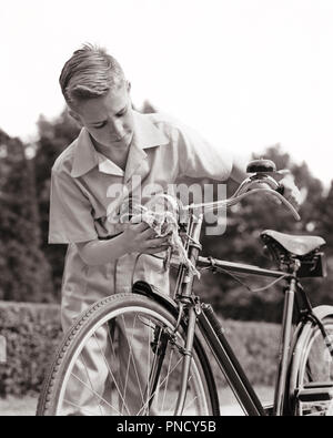1940s BLOND YOUNG TEENAGE BOY POLISHING HEADLIGHT ON EXPENSIVE ENGLISH BICYCLE - b14957 HAR001 HARS ENGLISH B&W BIKES WIPING HEADLIGHT PRIDE ON POLISHING HEADLAMP STYLISH MAINTAINING JUVENILES LEATHER SEAT PRE-TEEN PRE-TEEN BOY BLACK AND WHITE CAREFUL CAUCASIAN ETHNICITY EXPENSIVE HAR001 OLD FASHIONED - Stock Image