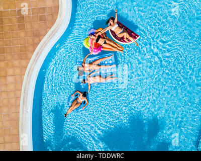 Coloured aerial background with group of friends woman caucasian people enjoying the summer holiday vacation at the blue water pool with trendy inflat - Stock Image
