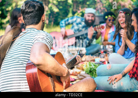 Young people doing picnic and playing guitar in park - Group of happy friends having fun during the weekend outdoor - Stock Image