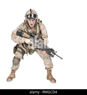 Soldier armed with assault service rifle crouching under fire and shouting orders. - Stock Image