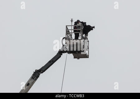 A camera man filming from the top of a crane platform - Stock Image
