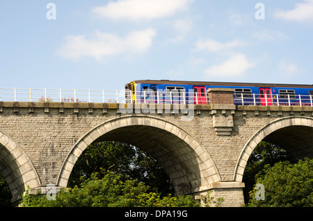 A brightly coloured train going over old stone bridge above tree tops, uk - Stock Image