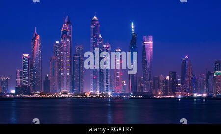 Wide view of Dubai skyline on the waterfront during the blue hour, with modern buildings and skyscrapers lit up. - Stock Image