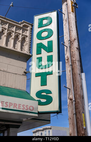 Large 'Donuts' sign next to a telephone pole - Stock Image