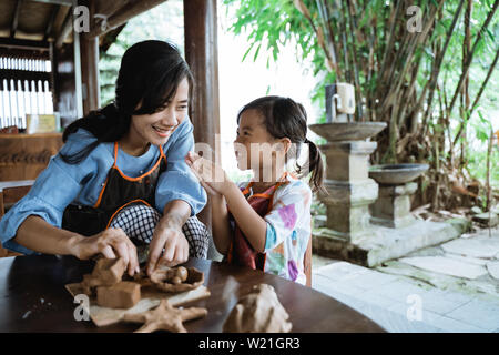 asian mother and daughter making pottery together with clay - Stock Image