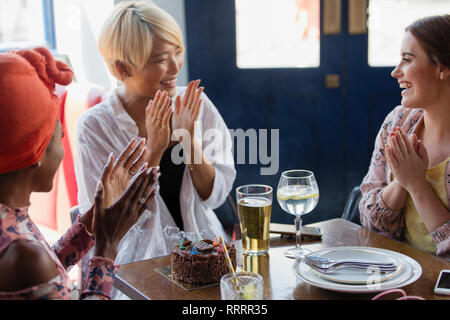 Happy young women friends celebrating birthday in restaurant - Stock Image