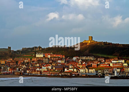 Scarborough's Castle lit by a winter afternoon's sun, sits majestically above South Bay and the town's harbour. - Stock Image