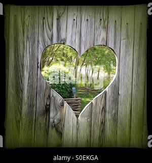 Garden view through heart-shaped hole in fence. - Stock Image