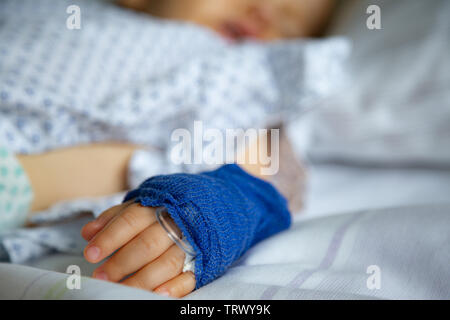 Sleeping sick child with peripheral venous line on his left hand in hospital - Stock Image