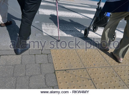 Elderly disabled people crossing road. - Stock Image