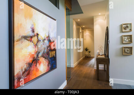 Framed abstract painting on grey wall of hallway with hickory wood floorboards inside a luxurious contemporary bungalow style home - Stock Image