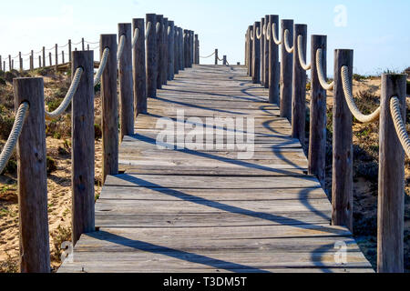 Looking through the centre of a wooden decking pathway down with rope railings on each side, the pathway is on sand dunes and heads up hill to the hor - Stock Image