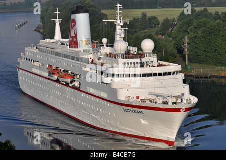 Cruiseship Deutschland steaming through the Kiel-Canal in the early morning. - Stock Image