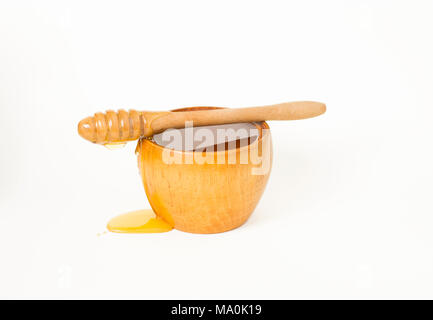 Honey in a wooden bowl and a special kind of a spoon for honey, a honey dipper. - Stock Image