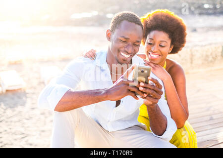 Cheerful black race diversity beautiful young couple use technology device modern phone outdoor with sun light in background - smile and happiness for - Stock Image