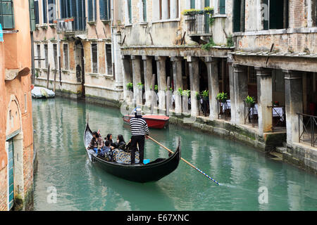 Venice, Italy. Gondolier and gondola with tourists on a canal. - Stock Image