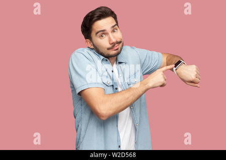 Portrait of sad handsome bearded young man in blue casual style shirt standing pointing and showing his smart watch and looking at camera. indoor stud - Stock Image