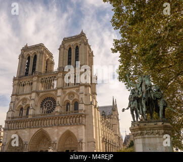 Color outdoor image of Notre Dame de Paris with the memorial statue of Charlemagne under an autumnal tree taken - Stock Image