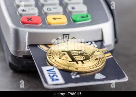 View of metal bitcoin with credit card and POS terminal.Concept image for cryptocurrency.Concept of bitcoin payment and cryptocurrency accepted here - Stock Image