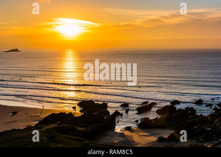 Surfers at sunset on Fistral Beach, Newquay, Cornwall, UK - Stock Image