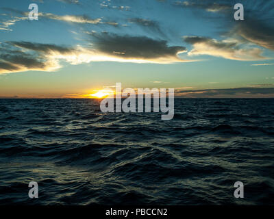 A white colored cloud blue Sky sunrise seascape over ocean water with water reflections.  Captured in Queensland, Australia. - Stock Image