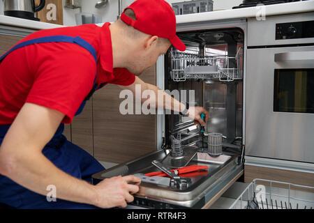 home appliance maintenance - repairman repairing dishwasher in kitchen - Stock Image