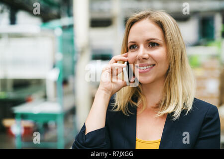 A portrait of a happy industrial woman engineer on the phone, standing in a factory. - Stock Image